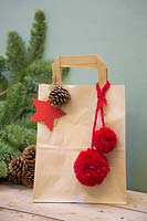 Brown paper christmas gift bag decorated with pine cone, felt star and wool pompoms