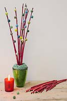 Red Cornus stems decorated with miniature wool pompoms