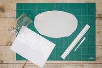 Materials for making clay lanterns - Modelling clay, glass jar, ruler, scalpel and a cityscape outline