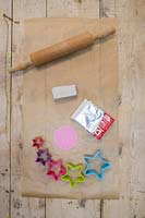 Making clay stars - Materials required are white modelling clay, silicone flower mould, star shape cutters, string, scissors, rolling pin and a skewer