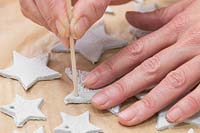 Making clay stars - Use a wooden skewer to create small holes on the tip of each star