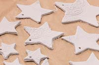 Making clay stars - A variety of different sized stars cut out from the modelling clay, with small holes added for hanging