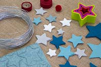 Making a felt christmas tree - Materials required are coloured felt, thin wire, pencil, a pom pom and star shaped cutters