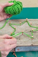 Making a christmas star decoration - Weave the green wool between the copper nails to recreate the star shape
