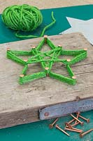 Making a christmas star decoration - A decorative plinth with a green woollen star wrapped around copper nails