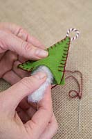 Making stitched felt christmas decorations - Insert the wool stuffing into the felt