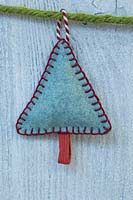 Making stitched felt christmas decorations - miniature christmas tree made from felt and decorative string, hanging against a wooden panel