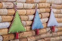Making stitched felt christmas decorations - miniature christmas trees made from felt and decorative string, hanging against a wine cork board