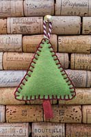 Making stitched felt christmas decorations - miniature christmas tree made from felt and decorative string, hanging against a wine cork board