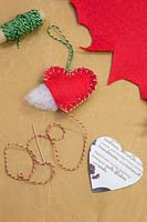 Making christmas decorations - Materials required are a heart template, needle, thread, wool and felt