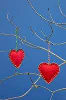 Red hearts stitched together with felt fabric, hanging from  twigs