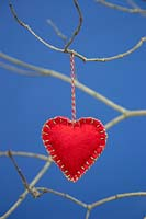 Red heart stitched together with felt fabric, hanging from  twig