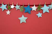 A variety of coloured felt stars hanging against a red background