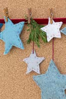 A variety of coloured felt stars hanging against a cork board
