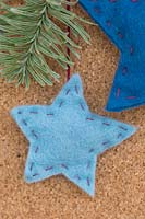A felt star decoration hanging against a cork board