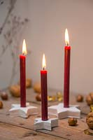 Red candles mounted inside clay stars, with hazlenuts and walnuts