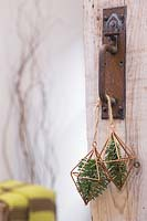 Copper prisms containing pine foliage, hanging from door handle