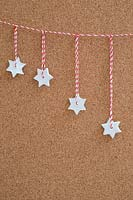 Miniature clay stars hanging from red and white striped string
