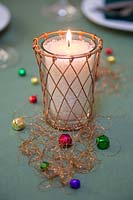Candle inside copper candle holder, with miniature baubles and copper thread
