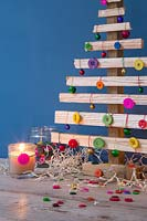 A wooden Christmas tree decorated with coloured buttons and baubles