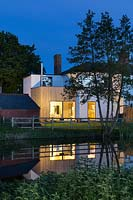 Riverside cottage lit up at night