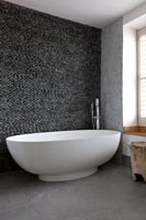 Contemporary bath with pebble wall