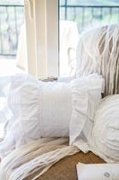 Detail of white lace cushion and accessories