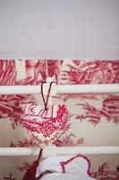 Detail of hanging heart ornament with patterned wallpaper