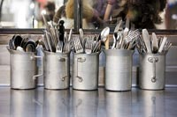 Metal jugs full of cutlery