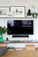 Wall mounted flat screen television in contemporary living room