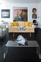 Plexiglass coffee tables in eclectic living room with colourful artwork