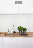 Kitchen worktop with sink and hexagonal shaped tiled splash backs