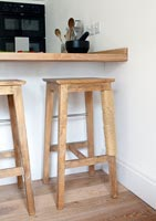 Wooden bar stools with a cat scratching post on one stool leg