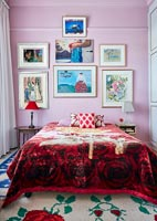 Classic colourful bedroom with display of framed paintings