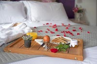 Breakfast tray on bed with rose petals and bathrobe