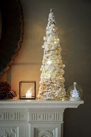 White Christmas tree and decorations on mantelpiece