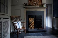 Wooden armchair next to wood burner and log store in fireplace