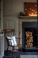 Wooden armchair next to log store in fireplace