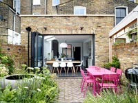 Pink outdoor dining table and view into kitchen through open bi-fold doors