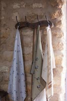 Wooden coat hanger on stone wall with variety of silk scarves