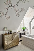 Gold cabinet and floral wallpaper in bathroom