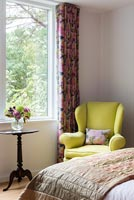 Yellow armchair by window in classic bedroom