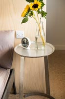 Small circular bedside table and vase of sunflowers