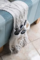 Knitted remote control holder draped over sofa