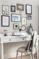 Classic desk and chair and display of framed pictures