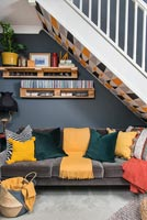 Sofa under staircase in colourful modern open plan sitting room