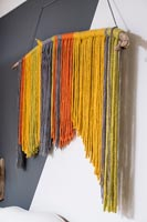 Display of colourful threads hanging on part painted wall