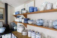Blue and white crockery on wooden shelf in cottage kitchen