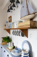 Toy boat and crockery in blue and white cottage kitchen