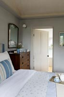 Country cottage bedroom with open internal door to bathroom